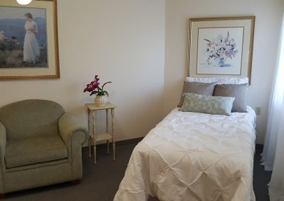 apartment with a comfortable chair and bed at Magnolia Gardens Senior Living