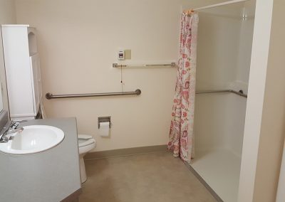 Apartment bathroom with a sink, cabinet, toilet, alert string, and wheelchair accessible shower at Magnolia Gardens Senior Living