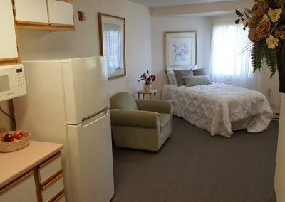 apartment with kitchenette, comfortable chair, and bed at Magnolia Gardens Senior Living